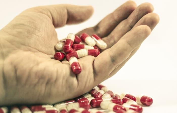 Hand mit Pillen für die Dosierung
